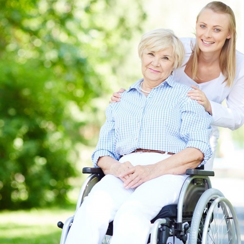Female caregiver and senior patient in a wheelchair looking at camera outside