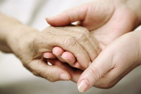 An elderly hand held by young hands