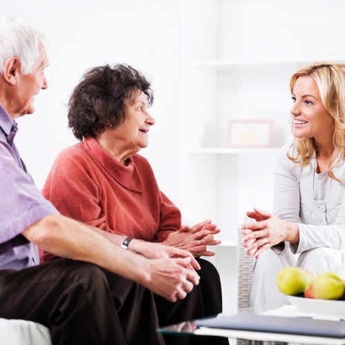 Elderly couple talking with a smiling younger woman