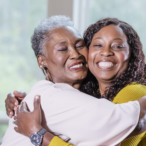 Senior African-American woman, adult daughter hugging