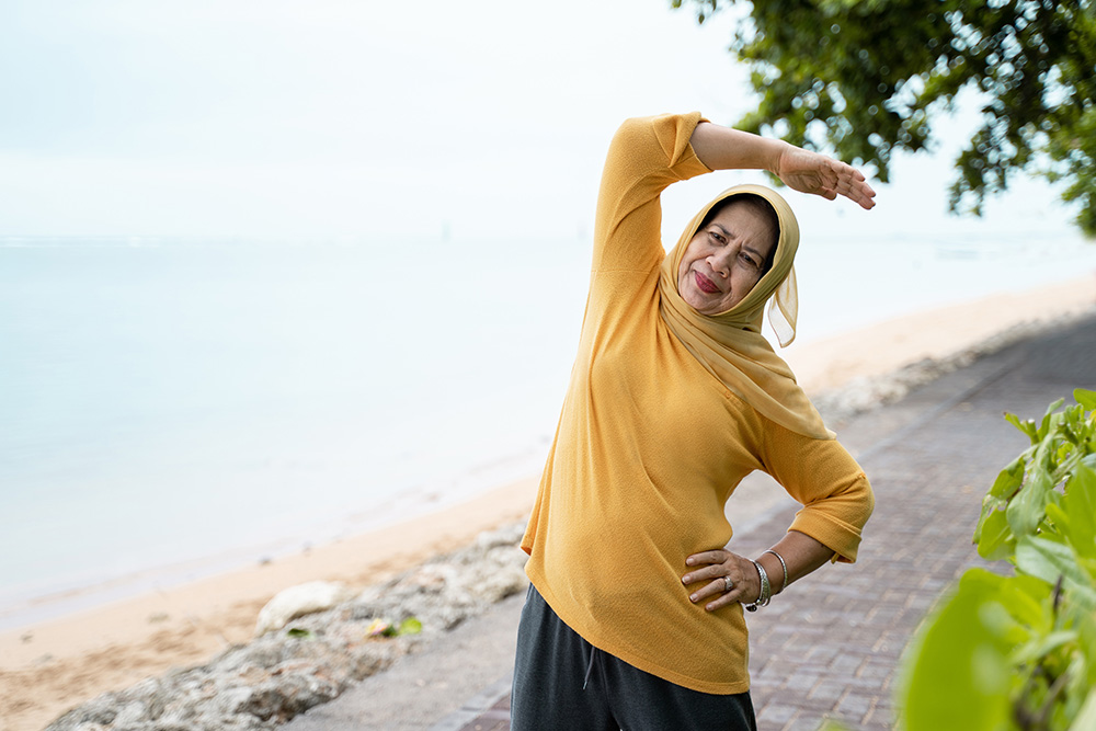 Older Muslim woman performing stretch exercises