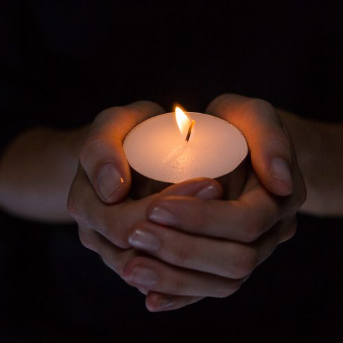 Hands holding candle on black background