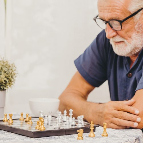 Elderly man playing Chess board game at home for training brain